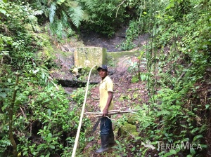 Local villager working on the pipe repair from the water source to the reservoir.